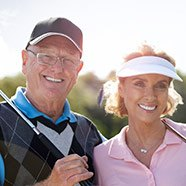 Couple outside golfing & smiling