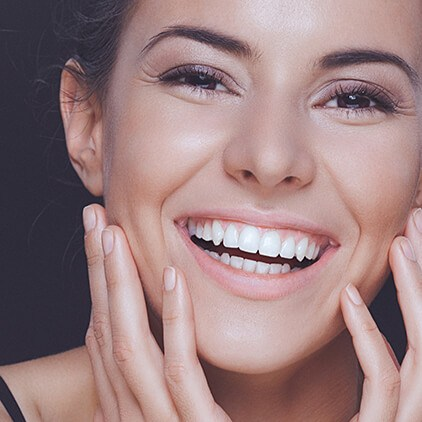 model smiling with hands on face