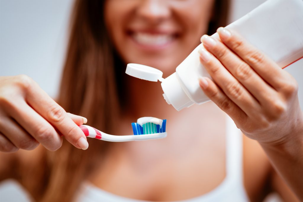 close-up of a woman putting paste on toothbrush