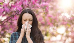 woman blowing nose with spring allergies