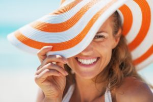 Woman in sunhat smiles after visiting her Kernersville dentist