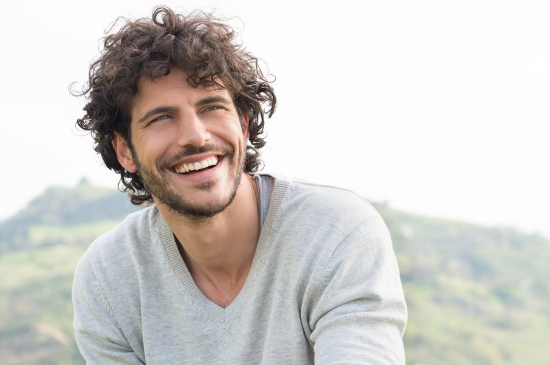a young male wearing a gray V-neck sweater and sitting outside smiling